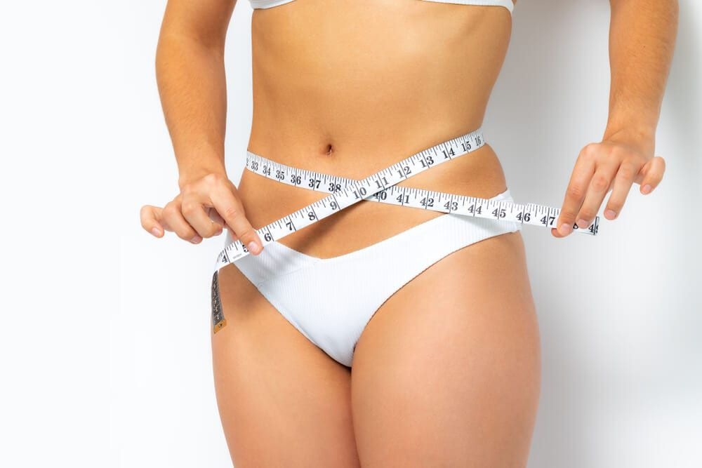 woman measuring stomach fat