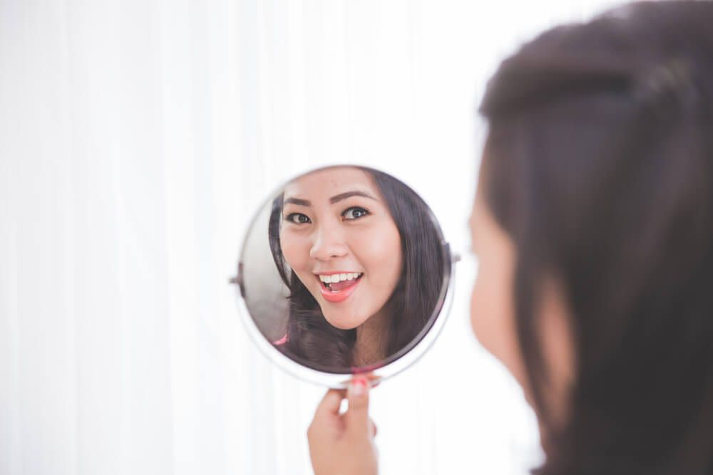 asian woman smiling in mirror